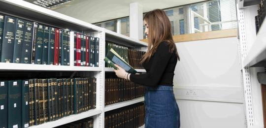 woman in front of bookshelf in library